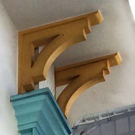painted yellow wood brackets with curved beam and backer boards