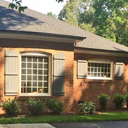 board and batten shutters with arch top on brick home