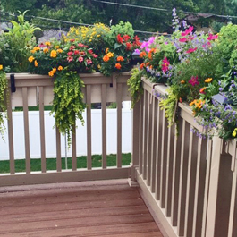 beige deck rail planters with hooks on corner of railing
