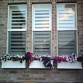 three close windows with flower boxes