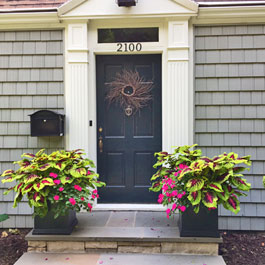 Two black square planters on front doorsteps display - coleus and pink impatiens