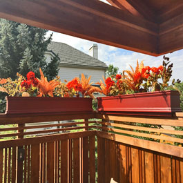 Red PVC planters on top of redwood backyard fencing with beautiful fall display and red flowers