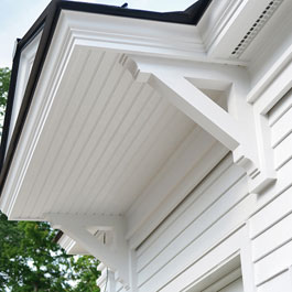 Large White Wooden Brackets Supporting Overhang Colonial