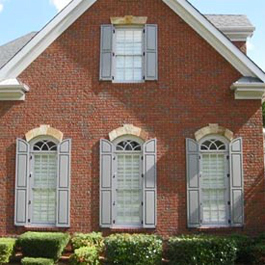 tall transom raised panel shutters with matching top panel on brick