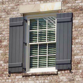 greyish blue board and batten shutters hinged on brick