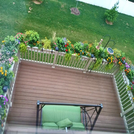 entire back deck rails completely wrapped in planters and flowers