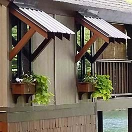 brown window boxes on lake house with bahama style window roof