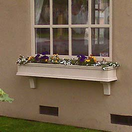 long beige window box on stucco with two support brackets
