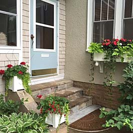 two square planters on steps with matching window box