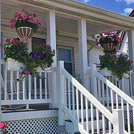 rail planters and hanging baskets on white porch