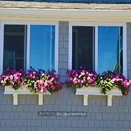 two adjacent white window boxes installed on shake siding