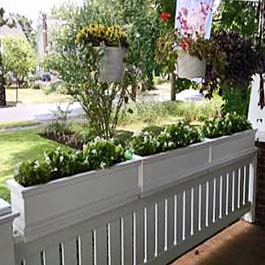 white flower boxes sit on top of porch railings
