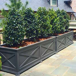 long, custom grey planter with X pattern design on front
